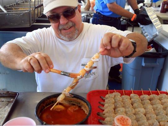 GABE HERNANDEZ/CALLER-TIMESPeter Grish prepares shrimp skewers for customers during Shrimporee on Saturday, June 11, 2016, in Aransas Pass.