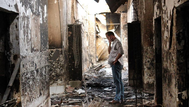 In this Friday, Oct. 16, 2015, file photo, an employee of Doctors Without Borders walks inside the charred remains of the organization's hospital after it was hit by a U.S. airstrike in Kunduz, Afghanistan.