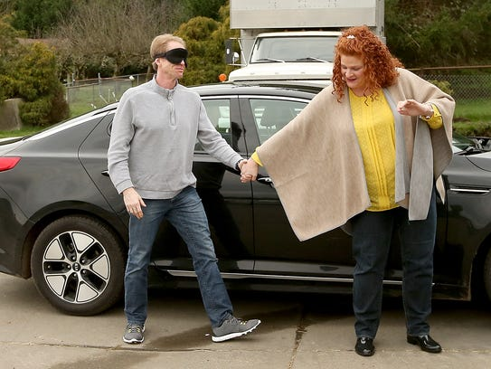 Tami Sims leads her blindfolded husband Don from the car to the cow barn at Blackjack Valley Farm in Port Orchard on Tuesday.