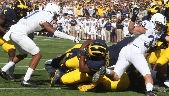 Michigan #80 Khalid Hill pushes his way into the end zone for the first score of the game during first half action.