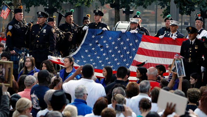 On Sept. 11, 2013, the World Trade Center flag is presented as friends and relatives of the victims of the 9/11 terrorist attacks gather at the National September 11 Memorial at the World Trade Center site.