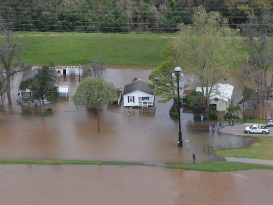 Houses located on Riverfront Street in Pineville near the Gillis-Long Bridge, also known as the Jackson Street Bridge, are surrounded by water from the Red River Thursday. Jason Lowentritt from Cenla Helicopters took The Town Talk staff photographer Melinda Martinez on an aerial tour Thursday of flooded areas.