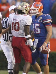 A referee moves in to separate FSU's Geno Hayes (10) and Florida quarterback Tim Tebow (15) after the play was whistled dead in the first half of their game in 2007.