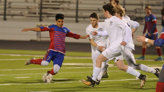 Cooper's Hector Tijerina (7) tries to shoot around a host of Bulldogs on Monday, Feb. 5, 2018 at Bulldog Stadium. Tijerina scored in the 2-1 win against Wylie.