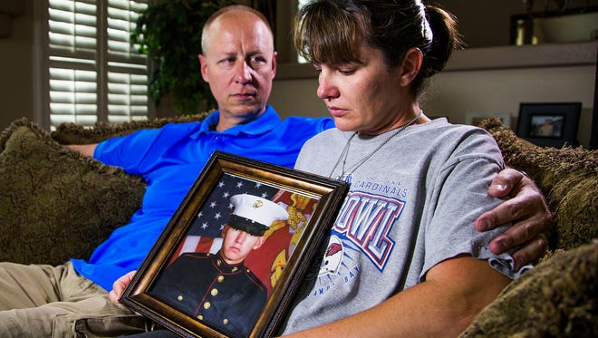 Jim and Andrea Hug, hold a photo of their son, Lance Corporal Jacob Hug, a videographer in the U.S. Marines. He was aboard a military helicopter that disappeared while performing a humanitarian mission in Nepal.