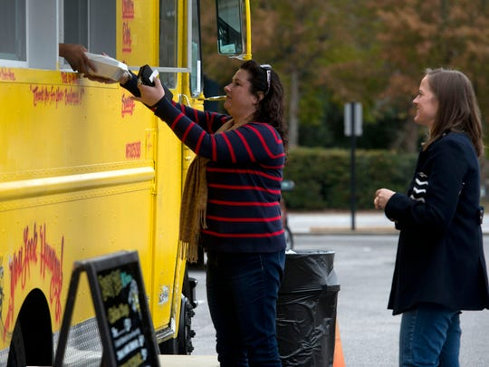 Brandy Bass, center,  grabs lunch at one of the food truck vendors in the parking lot of city hall Thursday Jan. 7, 2016, while, Jennie Waltrip, right, waits her food  order.  Under a new mayoral decree, food truck operations are now allowed on city hall property Thursday through Saturday from 8am-8p.m.