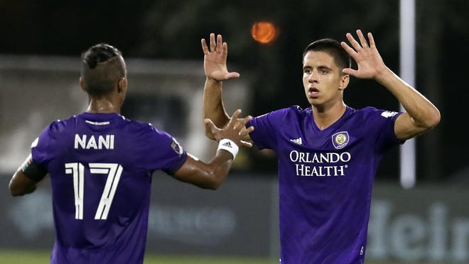 Orlando City defender Joao Moutinho, right, celebrates with teammate forward Nani (17) after he scored a goal against Los Angeles FC during the second half Friday in Orlando.