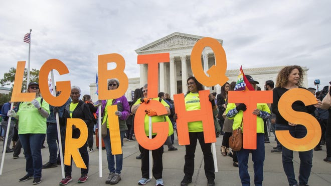 Supporters of the LGBT hold placards in front of the U.S. Supreme Court, Tuesday, Oct. 8, 2019, in Washington.  The Supreme Court is set to hear arguments in its first cases on LGBT rights since the retirement of Justice Anthony Kennedy. Kennedy was a voice for gay rights while his successor, Brett Kavanaugh, is regarded as more conservative.