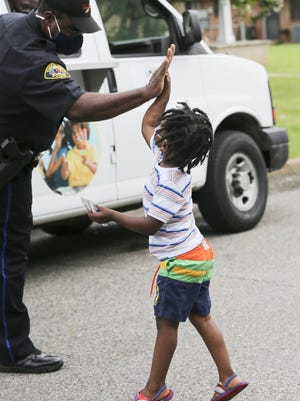 Ashton Thomas leaps to give a high five to a police officer.