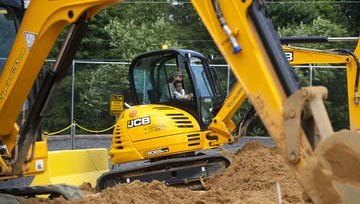 Visitors dig with a giant excavator at Diggerland in West Berlin.