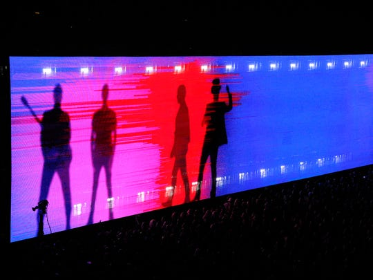 Silhouettes of U2 band members were displayed on a