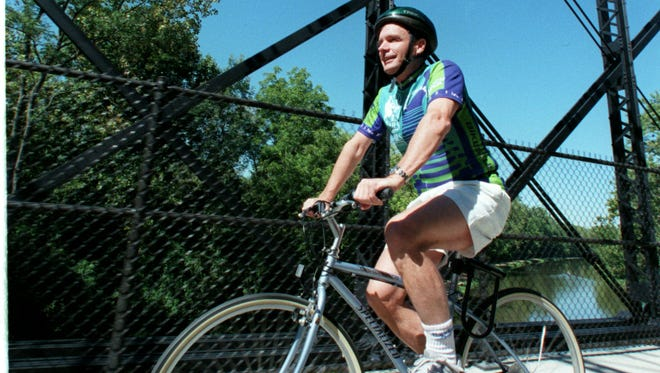 David Burwell, founder of Rails-to-Trails Conservancy, rides in 1999 along a trail that was converted from a CSX rail line.