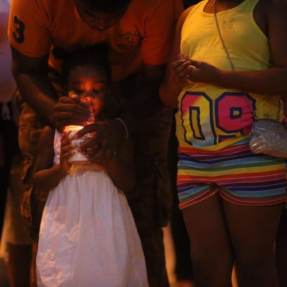 A child holds a candle at Friday's Light up the Night