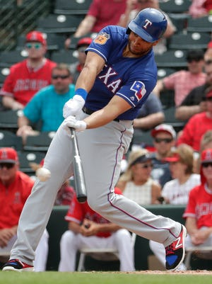 Texas Rangers first baseman James Loney follows through on a two-run base hit during the first inning against the Los Angeles Angels on March 22, 2017, in Tempe, Ariz.