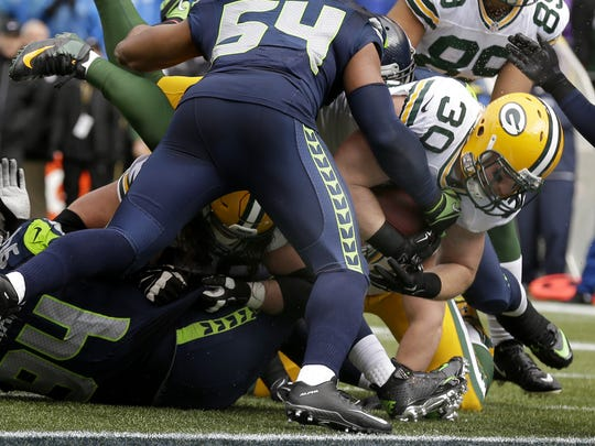 Green Bay Packers fullback John Kuhn dives for the goal line during the first quarter of Sunday's NFC championship game against the Seattle Seahawks at CenturyLink FIeld in Seattle.