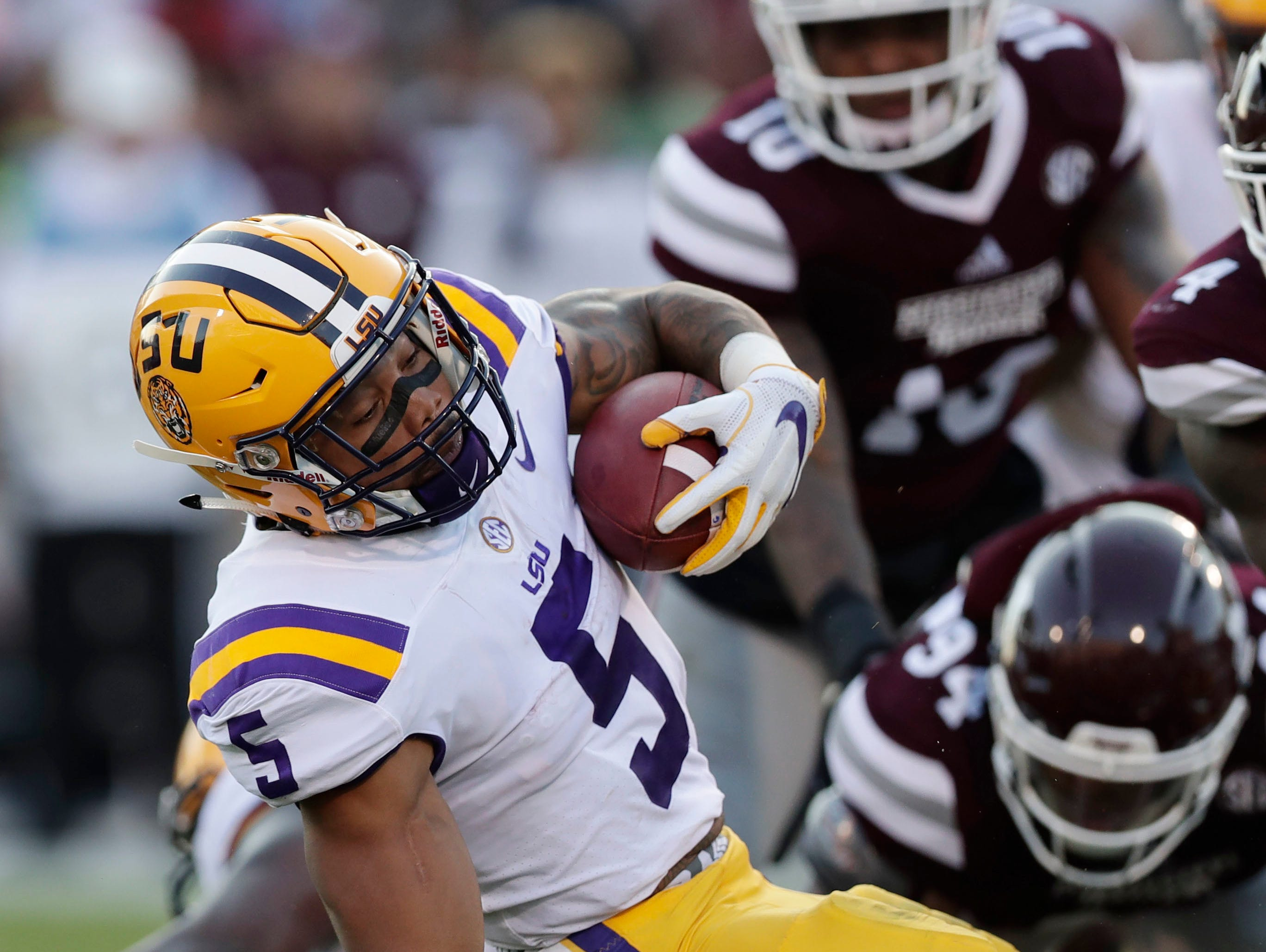LSU running back Derrius Guice (5) is tackled by Mississippi State defenders during the first half of their NCAA college football game against in Starkville, Miss., Saturday, Sept. 16, 2017.
