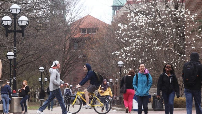 Students walk through the Ann Arbor campus of the University of Michigan on Tuesday April 22, 2014.
