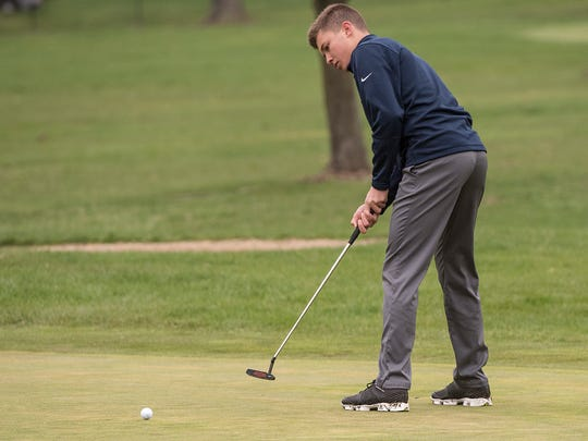Delivering a putt through a wet green is Livonia Stevenson's