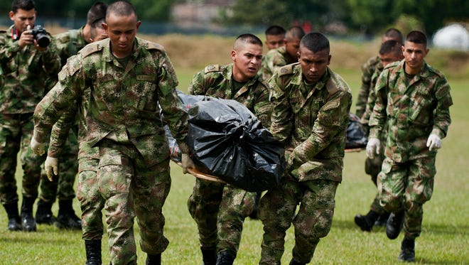Colombian soldiers unload from a helicopter the corpse of a FARC rebel leader on Aug. 10.