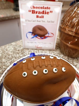 """A """"deflated"""" chocolate football called a """"Bradie"""" Ball is on display at Sarris Candy store in in Canonsburg, Pa., on Wednesday, Jan. 28, 2015. Owner Bill Sarris says they came up with the idea to poke fun at the controversy surrounding under-inflated footballs on Tuesday.  The display item isn't for sale.  (AP Photo/Keith Srakocic)"""