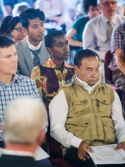New citizens listens to speakers before taking the