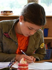 Cate Conaty, 12, works independently on a math problem