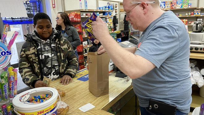 Russ Johnson, right, owner of the Short Stop Deli in the Town of Wallkill, puts Tyrell Glover's purchase in a paper bag on Thursday. Johnson is among the store owners worried there won't be enough paper bags when the state's plastic bag ban takes effect Sunday.