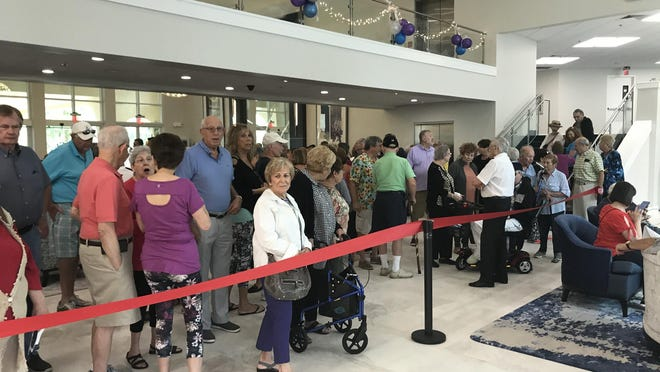 More than 100 residents attend a ribbon-cutting ceremony at Coral Lakes on Feb. 8 to mark the grand reopening of its social hall. The facility was closed for 8 months while the work was done.