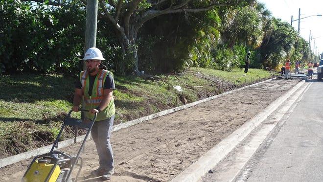 Construction crews prep a sidewalk Friday on the $8.37 million project to add bike lanes along a 3.7-mile stretch of Boynton Beach Boulevard.