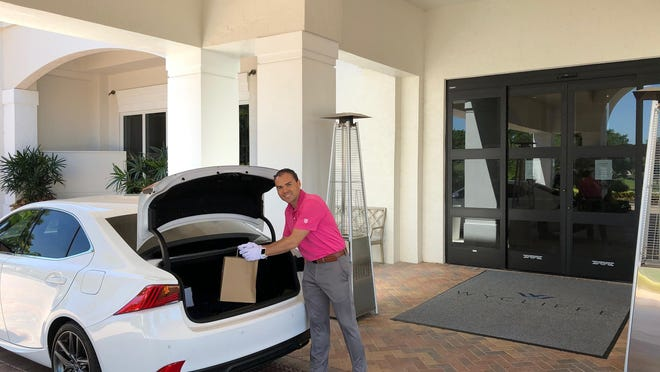 A worker at Wycliffe Country Club west of Lake Worth Beach puts a meal into the trunk of a car of a resident taking advantage of a pick up and delivery program designed to keep residents from leaving the community. The resident and staff do not have any contact with each other.