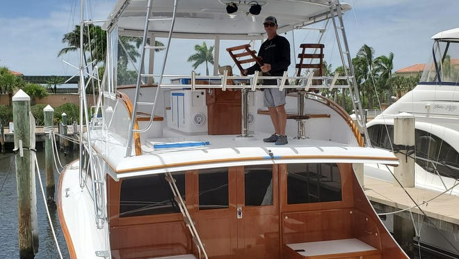 Captain Jimmy Hall secures potential projectiles on the 60-foot 'Tripletale' at Jupter Yacht Club & Marina in advance of Hurricane Isaias.