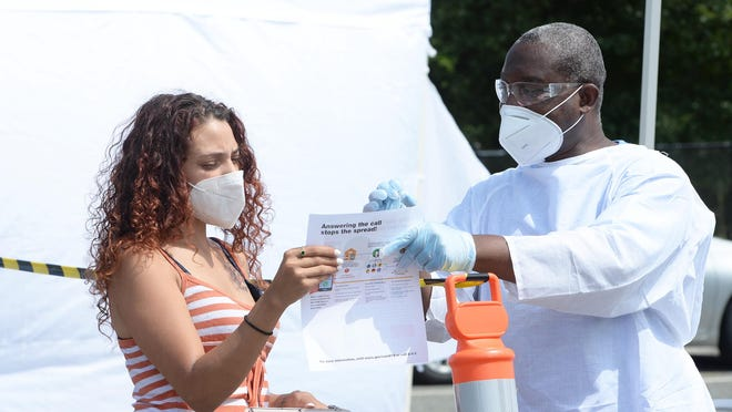 In this Aug. 13, 2020, file photo, Yaritza Higgns, 27, gets paperwork from Reynold Fareau, a care access navigator at BAMSI, at the free, walk-up coronavirus testing site at the Crescent Court public housing complex in Brockton, run by Brockton Area Multi-Services Inc. through the state's Stop the Spread program.