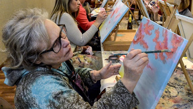 Julia Pate, left, works on adding shadows and highlights to the clouds on her painting during past a Blushing Artiste class at Garden City Arts. A few in-person classes are returning to GCA, with smaller numbers of participants due to the COVID-19 pandemic.