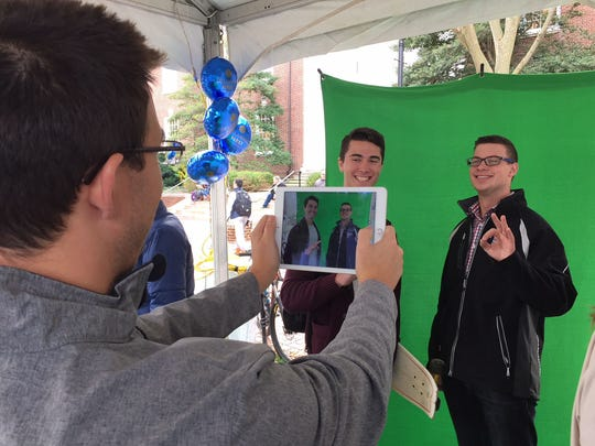Joe Charpentier (foreground left) takes a picture of Evan Hughes (background left) and Josh Brown (right) that'll go up on a mosaic wall.
