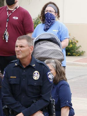 Brownwood Police Chief Ed Kading kneels outside City Hall as protesters lie face down on the pavement.