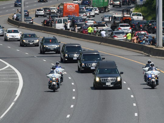 The funeral procession for Officer Amy Caprio passes below the Dulaney Valley Road bridge on the outer loop of I-695 in Towson, Md. Caprio was run over by a Jeep while investigating a burglary Monday at a house in Perry Hall. Four teenagers are charged with murder. (Jerry Jackson/The Baltimore Sun via AP)