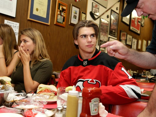 New Jersey Devils' Nico Hischier talks with an owner of Hobby's Deli, Marc Brummer, in Newark, N.J., Monday, June 26, 2017. The 18-year-old center was the first Swiss-born player to be drafted first overall in a NHL draft. (AP Photo/Seth Wenig)