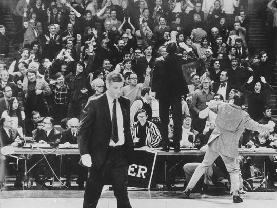 Glenn Hughes, father of Wisconsin's Kim and Kerry, expresses his feelings to Marquette coach Al McGuire (standing on table) after the Warriors pulled off an improbable victory in 1974.