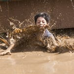 A kid splashes down off a slide into a mud pool during Mighty Mud Mania at Chaparral Park, Saturday, June 6, 2015, in Scottsdale, Ariz.