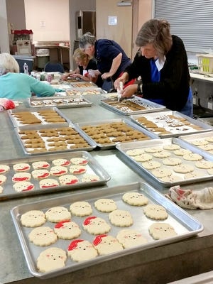 """Volunteers prepare cookies for the annual """"Cookie Walk"""" at St. Peter the Fisherman Catholic Church."""
