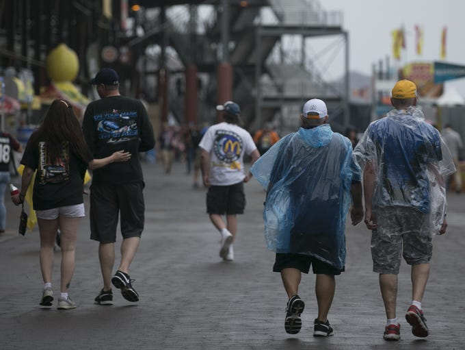 Fans walk through a light rain at ISM Raceway at the