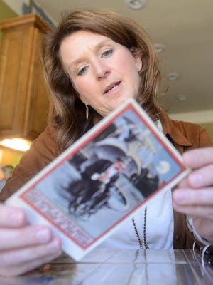 Susan McCarter reads the back of one of her vintage Valentine's Day postcards at her home in Jackson.