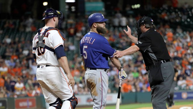 Home plate umpire Gerry Davis, right, steps in front of Texas Rangers' Mike Napoli (5) as Houston Astros catcher Brian McCann (16) walks toward them after a close pitch thrown by starting pitcher Lance McCullers Jr. during the sixth inning of a baseball game, Monday, May 1, 2017, in Houston.