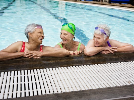 Smiling senior woman swimmers in pool