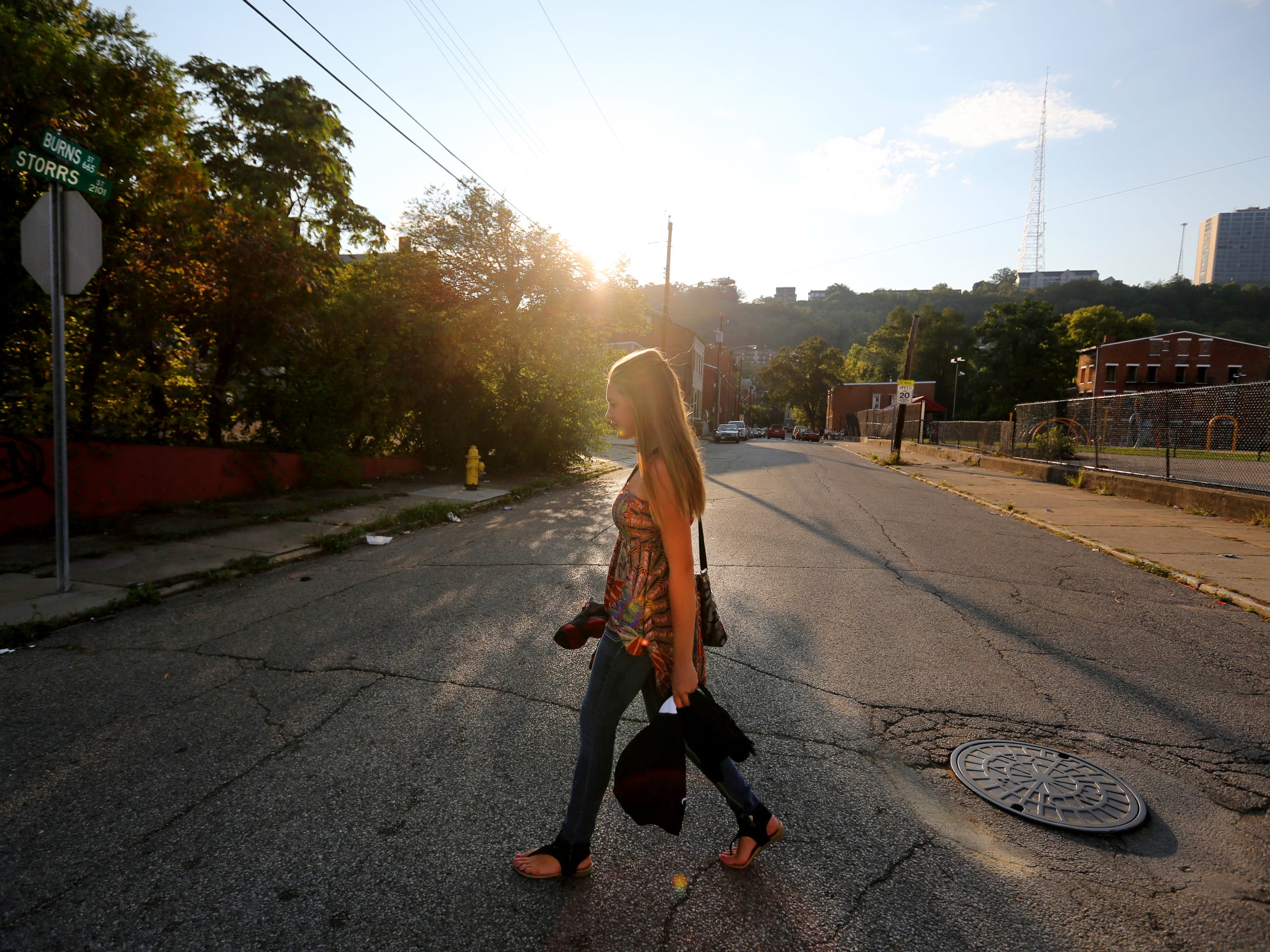Kelsey McLean, 16, walks home from a volleyball game at Olyer School in Lower Price Hill where she is a junior. Once she checks in at home, she says she often wonders the neighborhood for hours looking for something to do.