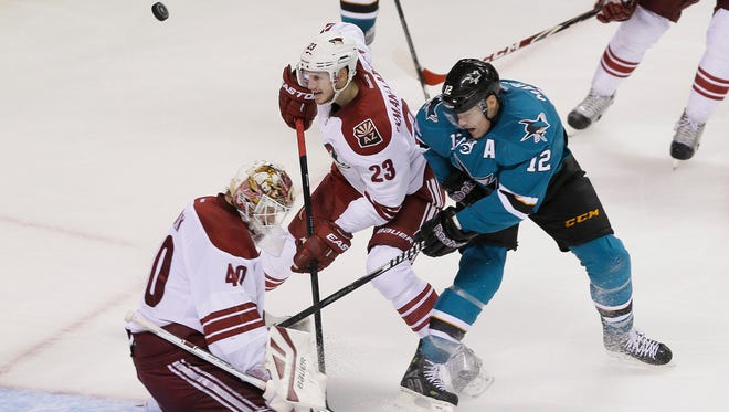 San Jose Sharks center Patrick Marleau (12) battles for the puck against Arizona Coyotes goalie Devan Dubnyk (40) and defenseman Oliver Ekman-Larsson (23) during the second period of an NHL hockey game Saturday, Nov. 22, 2014, in San Jose, Calif.