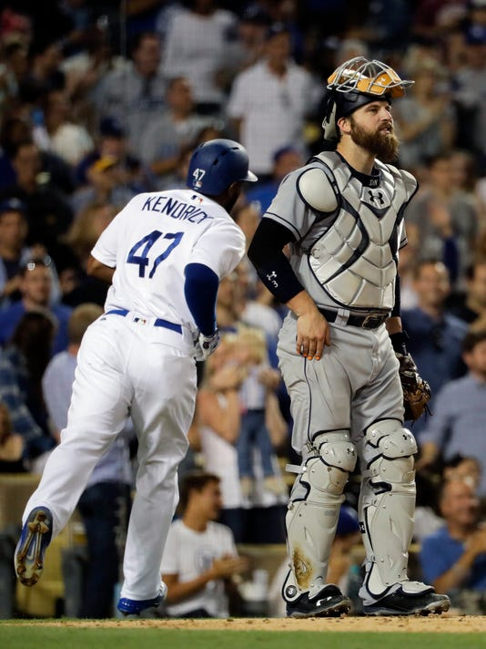 San Diego Padres catcher Derek Norris, right, stands near home plate as Los Angeles Dodgers' Howie Kendrick makes his way toward the dugout after hitting a home run during the third inning of a baseball game Friday, July 8, 2016, in Los Angeles. (AP Photo/Jae C. Hong)