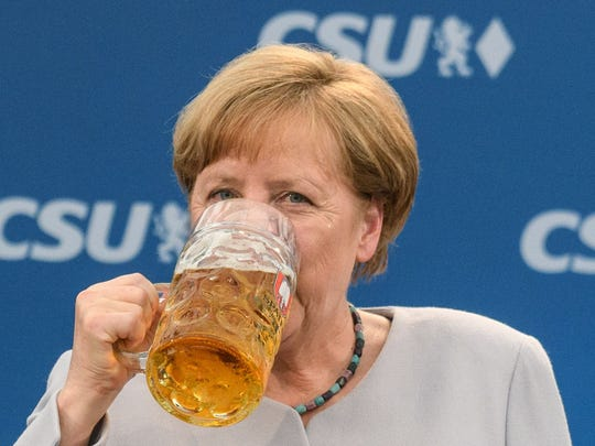 German Chancellor Angela Merkel takes a sip of beer after delivering a speech during a joint campaigning event of the Christian Democratic Union (CDU) and the Christion Social Union (CSU) in Munich, southern Germany, on May 27, 2017.