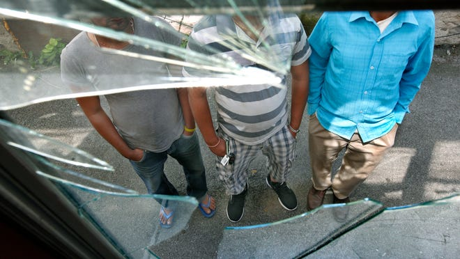 Bhutanese refugees, from left, Puspa Acharya, Bala Acharya and Ganga Acharya stand Friday in front of one of the windows broken at their Rochester home Thursday by a crowd of young men. Their faces are blocked because they fear possible retaliation .