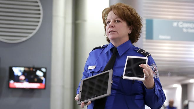 Transportation security officer Angie Melton explains on Tuesday what electronic items all standard passengers will be required to put in bins for X-ray screenings by the start of 2018. She shared the information at a news conference at Green Bay-Austin Straubel Airport in Ashwaubenon.